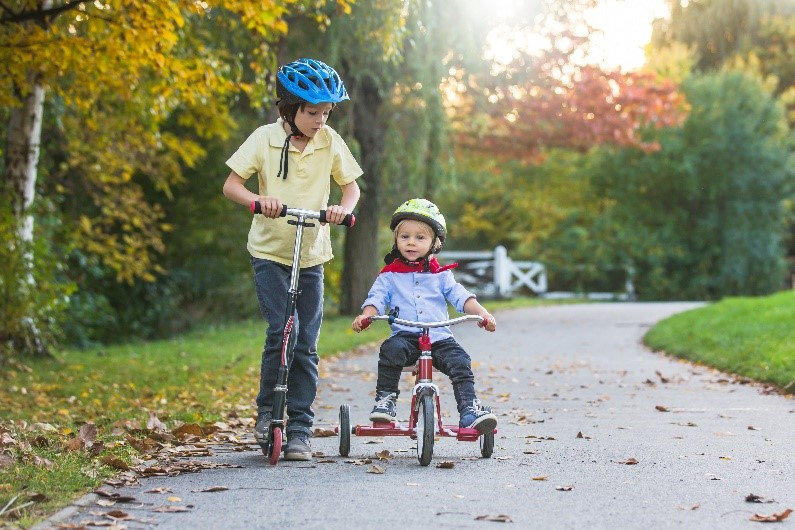 two boys riding a scooter and a bike